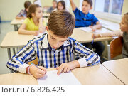 group of school kids writing test in classroom. Стоковое фото, фотограф Syda Productions / Фотобанк Лори