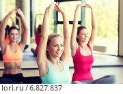 Купить «group of smiling women stretching in gym», фото № 6827837, снято 7 июня 2014 г. (c) Syda Productions / Фотобанк Лори