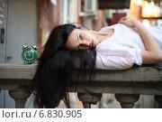 Красивая брюнетка на каменном парапете с будильником. Стоковое фото, фотограф Ivanikova Tatyana / Фотобанк Лори