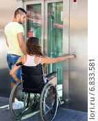 Купить «Couple with wheelchair in elevator», фото № 6833581, снято 19 апреля 2019 г. (c) Яков Филимонов / Фотобанк Лори