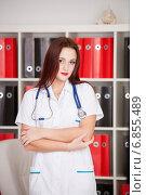 Купить «Молодой доктор с фонендоскопом приветствует клиентов в клинике», фото № 6855489, снято 8 ноября 2014 г. (c) Литвяк Игорь / Фотобанк Лори