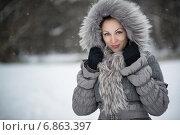 Красивая девушка в меховом капюшоне стоит под падающим снегом и улыбается. Стоковое фото, фотограф Андрей Шарашкин / Фотобанк Лори