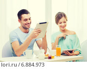 Купить «smiling couple with tablet pc reading news», фото № 6884973, снято 9 марта 2014 г. (c) Syda Productions / Фотобанк Лори