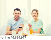 Купить «smiling couple with smartphones reading news», фото № 6884977, снято 9 марта 2014 г. (c) Syda Productions / Фотобанк Лори
