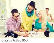 Купить «smiling team with printed photos working in office», фото № 6886853, снято 17 мая 2014 г. (c) Syda Productions / Фотобанк Лори