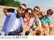 Купить «group of smiling friends with smartphone outdoors», фото № 6887013, снято 10 августа 2014 г. (c) Syda Productions / Фотобанк Лори