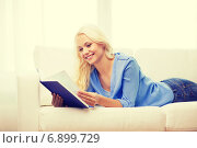 Купить «smiling woman reading book and lying on couch», фото № 6899729, снято 6 февраля 2014 г. (c) Syda Productions / Фотобанк Лори
