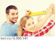 Купить «couple building using spirit level to measure», фото № 6900141, снято 26 января 2014 г. (c) Syda Productions / Фотобанк Лори