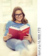 Купить «smiling teenage girl reading book on couch», фото № 6900173, снято 26 февраля 2014 г. (c) Syda Productions / Фотобанк Лори