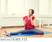 smiling teenage girl streching on floor at home. Стоковое фото, фотограф Syda Productions / Фотобанк Лори