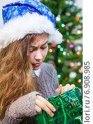 Купить «Молодая женщина с недоумением смотрит в подарочный новогодний пакет», фото № 6908985, снято 28 декабря 2014 г. (c) Кекяляйнен Андрей / Фотобанк Лори