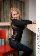 Стройная миниатюрная блондинка сидит на высоком стуле у барной стойки и улыбается. Стоковое фото, фотограф Андрей Шарашкин / Фотобанк Лори
