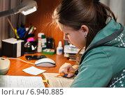 Купить «Девочка выполняет домашнюю работу сидя за столом дома», эксклюзивное фото № 6940885, снято 26 января 2015 г. (c) Игорь Низов / Фотобанк Лори