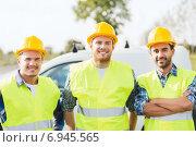 Купить «group of smiling builders in hardhats outdoors», фото № 6945565, снято 21 сентября 2014 г. (c) Syda Productions / Фотобанк Лори