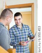 Купить «Service employee with tenant at doorway», фото № 6950453, снято 18 августа 2018 г. (c) Яков Филимонов / Фотобанк Лори