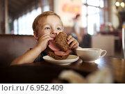 Купить «Мальчик ест бутерброд с колбасой в кафе», фото № 6952409, снято 27 июля 2014 г. (c) Данил Руденко / Фотобанк Лори