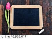 Купить «Грифельная доска, мелок и тюльпан на деревянном столе», фото № 6963617, снято 31 января 2014 г. (c) Наталия Кленова / Фотобанк Лори