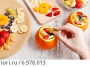Купить «Orange filled with fruit salad - making of», фото № 6978013, снято 19 июня 2019 г. (c) BE&W Photo / Фотобанк Лори