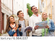 Купить «group of friends with city guide, map and camera», фото № 6984037, снято 14 июня 2014 г. (c) Syda Productions / Фотобанк Лори