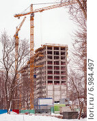 Купить «Строительство многоэтажного жилого дома в Москве (вертикально)», эксклюзивное фото № 6984497, снято 5 февраля 2015 г. (c) Константин Косов / Фотобанк Лори