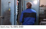 Купить «Старший электромеханик проверяет короб с кабелями, проводами, переключателями и выключателями», видеоролик № 6985949, снято 10 января 2015 г. (c) Кекяляйнен Андрей / Фотобанк Лори