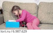 Купить «Девочка играет в игрушки на диване, собирает в голубую коробку», видеоролик № 6987629, снято 12 января 2015 г. (c) Кекяляйнен Андрей / Фотобанк Лори