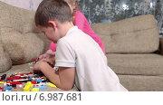 Купить «Двое детей играют в детский конструктор на диване в домашней обстановке», видеоролик № 6987681, снято 12 января 2015 г. (c) Кекяляйнен Андрей / Фотобанк Лори