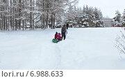Родители с детьми на надувной ватрушке идут через зимний парк. Стоковое видео, видеограф Кекяляйнен Андрей / Фотобанк Лори
