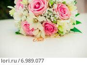 Купить «Обручальные кольца на белом фоне  букета розовых роз», фото № 6989077, снято 12 августа 2014 г. (c) Михаил Смиров / Фотобанк Лори
