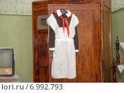 Парадная советская школьная форма с пионерским галстуком висит на двери старого шкафа. Стоковое фото, фотограф Pukhov K / Фотобанк Лори