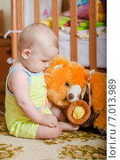 Маленький ребёнок играет на полу с оранжевым медведем. Стоковое фото, фотограф Евгения Устиновская / Фотобанк Лори