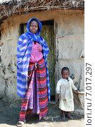 Купить «Деревня племени масаи недалеко от города Аруша в Танзании. Молодая чернокожая женщина в драпированной накидке и девочка двух лет стоят перед входом в хижину», фото № 7017297, снято 14 февраля 2008 г. (c) Владимир Григорьев / Фотобанк Лори