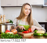 blonde woman in apron slicing pepper at table. Стоковое фото, фотограф Яков Филимонов / Фотобанк Лори