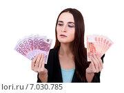 Молодая женщина вопросительно смотрит на купюры рублей и евро. Стоковое фото, фотограф Анна Милованова / Фотобанк Лори