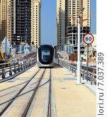 Трамвай в современном дизайне едет по рельсам г. Дубай, ОАЭ, фронтальный вид (2014 год). Редакционное фото, фотограф SevenOne / Фотобанк Лори