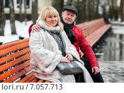 Купить «Счастливая пара. Симпатичные мужчина и женщина сидят в обнимку на длинной скамейке зимой на свежем воздухе», эксклюзивное фото № 7057713, снято 23 февраля 2015 г. (c) Игорь Низов / Фотобанк Лори