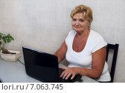 Улыбающаяся женщина в возрасте за ноутбуком. Стоковое фото, фотограф Tanya Ischenko / Фотобанк Лори