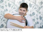 Купить «Веселый подросток сидит дома с барабаном и барабанными палочками», фото № 7063873, снято 25 февраля 2015 г. (c) Володина Ольга / Фотобанк Лори