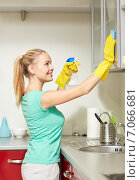 Купить «happy woman cleaning cabinet at home kitchen», фото № 7066681, снято 25 января 2015 г. (c) Syda Productions / Фотобанк Лори