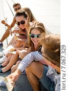Купить «group of smiling friends sitting on city square», фото № 7067329, снято 20 июля 2014 г. (c) Syda Productions / Фотобанк Лори