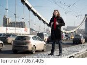 Молодой человек с длинными волосами в черном полупальто  стоит на Крымском мосту возле проезжей части (2015 год). Редакционное фото, фотограф Анастасия Кузьмина / Фотобанк Лори
