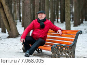 Купить «Взрослый мужчина в красной куртке сидит на лавочке в зимнем парке», эксклюзивное фото № 7068005, снято 23 февраля 2015 г. (c) Игорь Низов / Фотобанк Лори