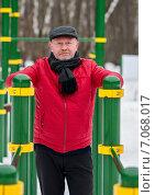 Купить «Немолодой мужчина стоит возле снаряда  в спортивном городке», эксклюзивное фото № 7068017, снято 23 февраля 2015 г. (c) Игорь Низов / Фотобанк Лори
