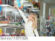 Купить «Девочка выбирает школьные принадлежности в магазине», фото № 7077025, снято 30 марта 2014 г. (c) Наталья Давыдова / Фотобанк Лори