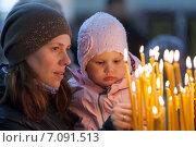 Купить «Молодая женщина с дочерью ставят свечку в церкви», фото № 7091513, снято 2 мая 2014 г. (c) EugeneSergeev / Фотобанк Лори