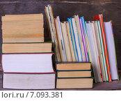 Стопка книг разного размера на деревянном фоне. Стоковое фото, фотограф Marina Kutukova / Фотобанк Лори