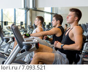Купить «men working out on exercise bike in gym», фото № 7093521, снято 28 сентября 2014 г. (c) Syda Productions / Фотобанк Лори