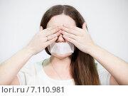 Купить «Девушка с наклеенной лентой на рот и прикрытыми руками глазами», фото № 7110981, снято 28 февраля 2015 г. (c) Кекяляйнен Андрей / Фотобанк Лори