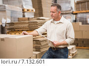 Купить «Warehouse worker checking his list on clipboard», фото № 7132601, снято 6 сентября 2014 г. (c) Wavebreak Media / Фотобанк Лори