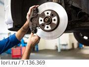 Купить «Focused mechanic adjusting the wheel», фото № 7136369, снято 4 октября 2014 г. (c) Wavebreak Media / Фотобанк Лори